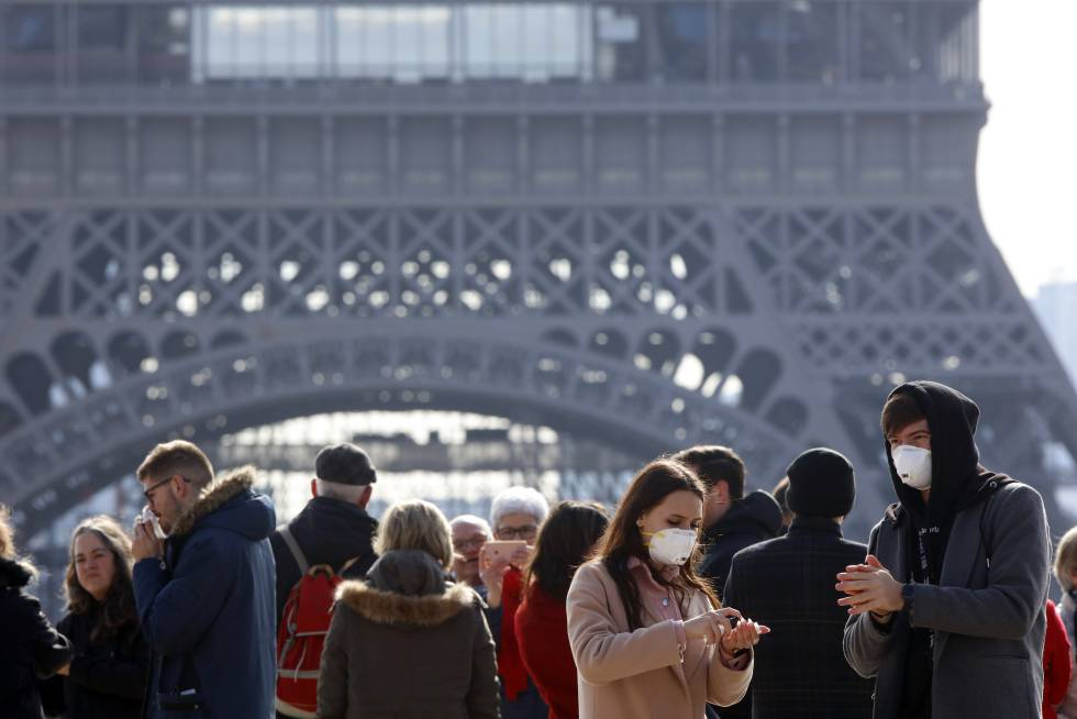 Two tourists with a mask to avoid the coronavirus, yesterday in front of the Eiffel Tower in Paris.