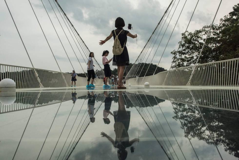 Varios turistas pasean por el puente.