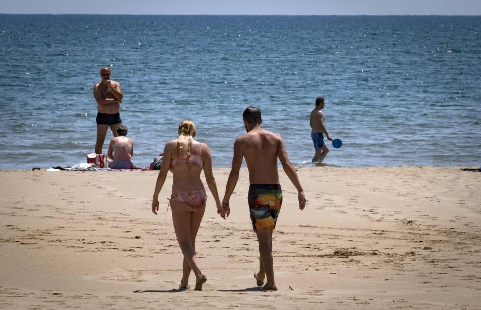 Una pareja camina por la playa, en una imagen de archivo.
