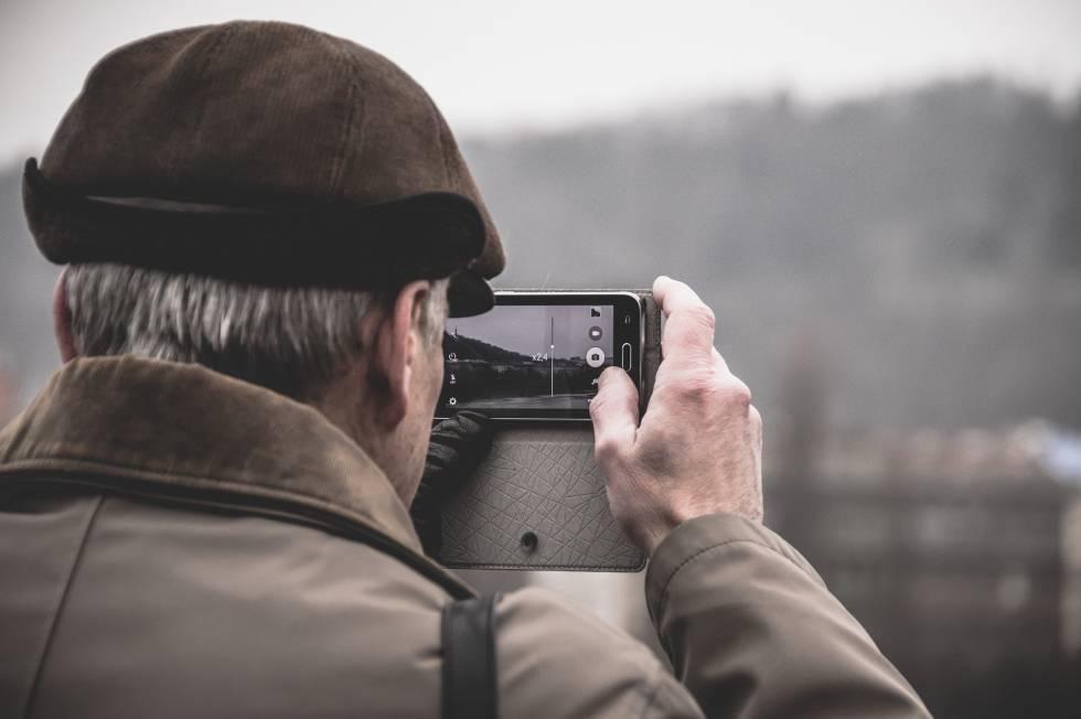 Una persona mayor de 60 años toma una foto con un móvil.