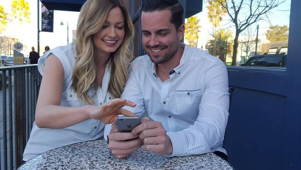 Una pareja utiliza un teléfono móvil.