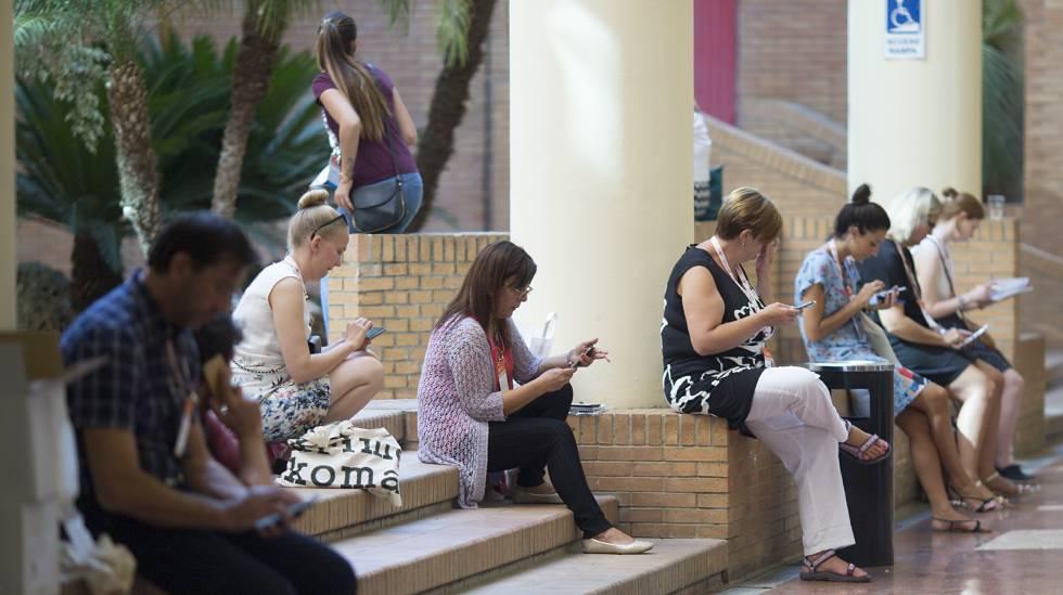 Participantes en un congreso en Sevilla consultan sus móviles.