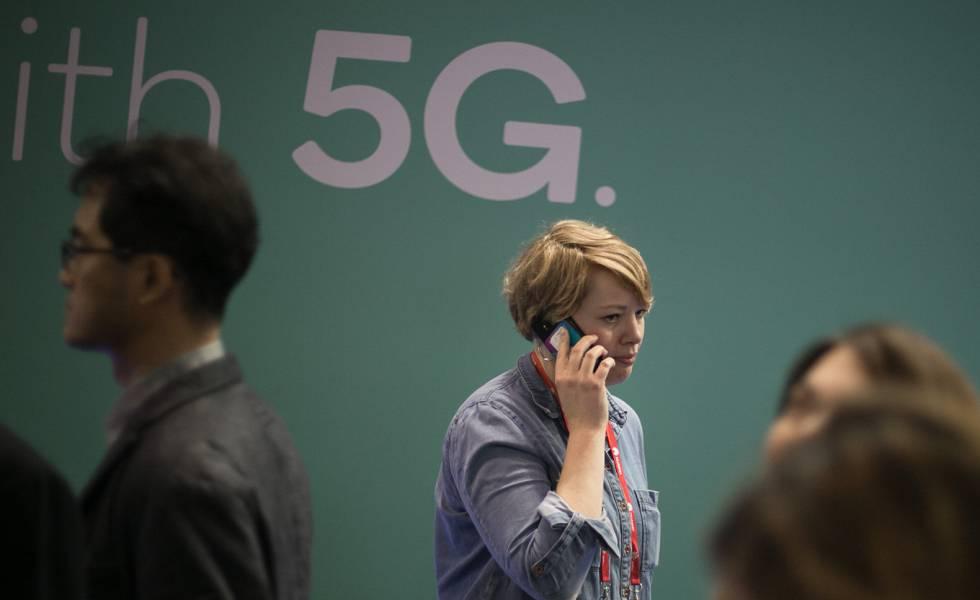 Una mujer camina mientras habla por telefono mientras pasa junto a un anuncio de tecnologia 5G.