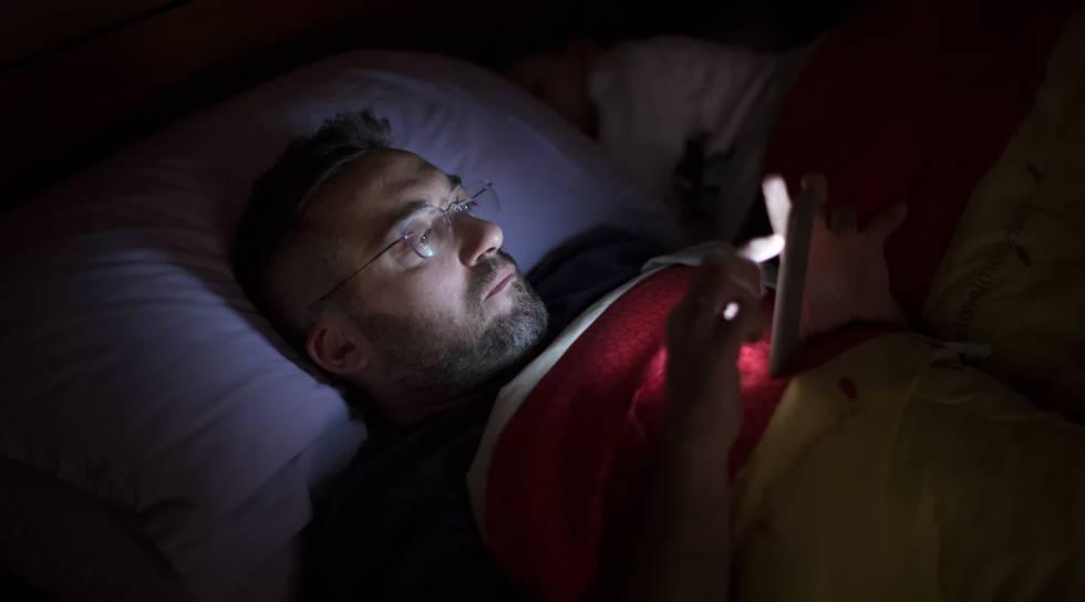 Un hombre lee a oscuras con su smartphone en la cama.