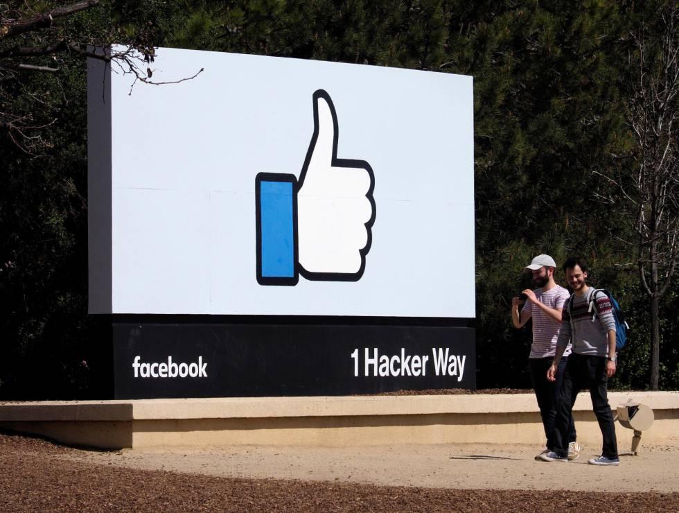 Dos hombres caminan junto a un icono de Facebook en Menlo Park, California, EE.UU., el 30 de marzo del 2018.