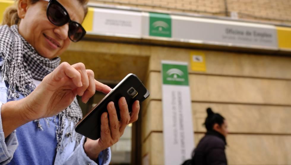 Una desempleada consulta su móvil tras pasar por una oficina de empleo en Sevilla esta semana.