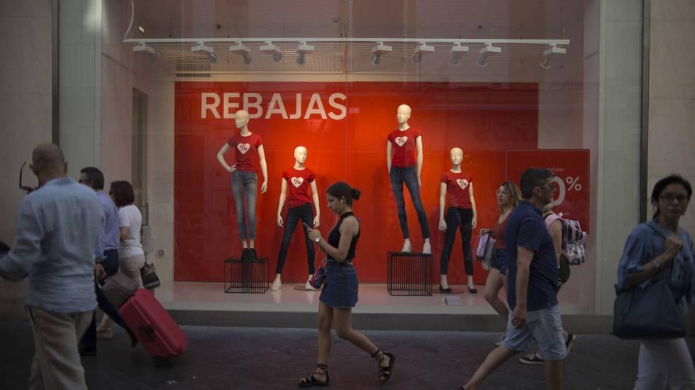 Una joven consulta en Sevilla el móvil frente a un comercio en temporada alta de ventas y contratación temporal.