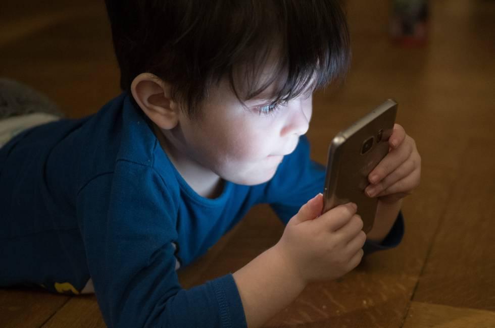 Un niño juega con el teléfono móvil.