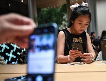 Una joven observa un iPhone.