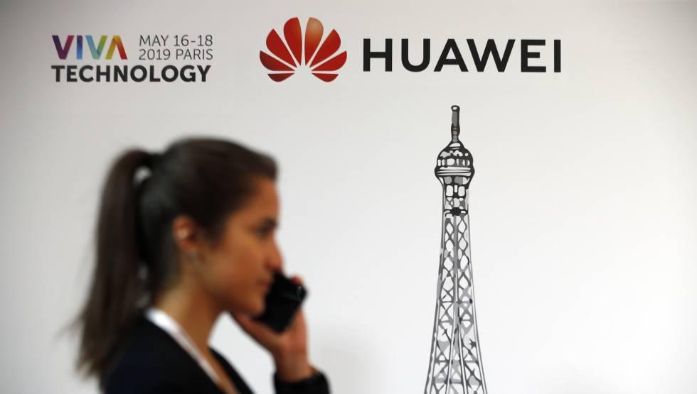 Una usuaria de móvil, junto a un cartel de Huawei en la reciente feria tecnológica celebrada en París.