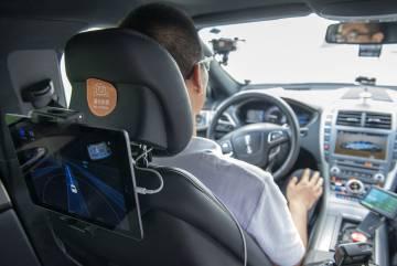 El conductor de seguridad no toca el volante mientras la pantalla del pasajero muestra el camino y los obstáculos.
