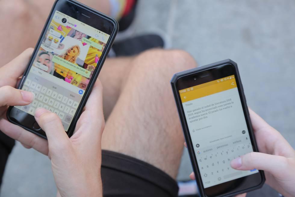 Dos usuarios escriben en sus móviles.