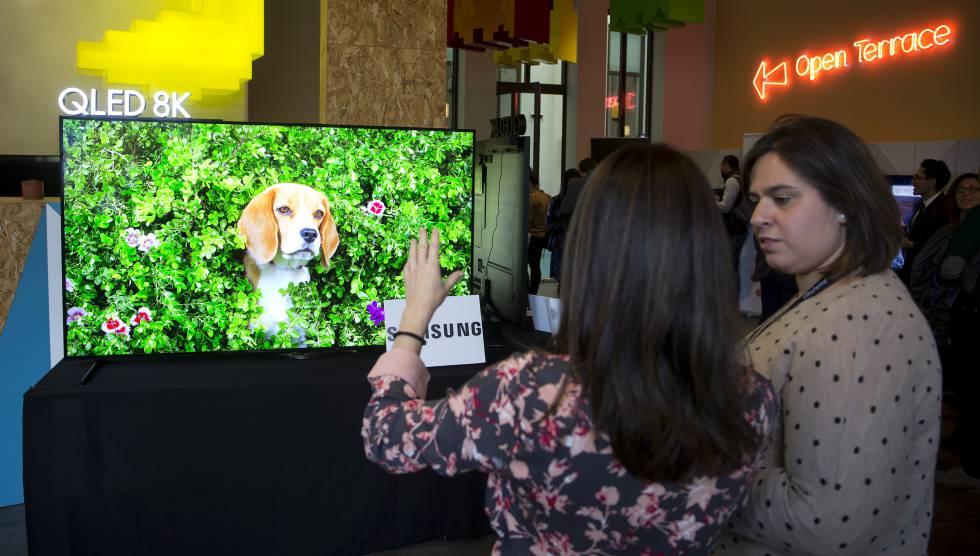 Dos asistentes al 4K HDR Summit, frente a un televisor 8K.