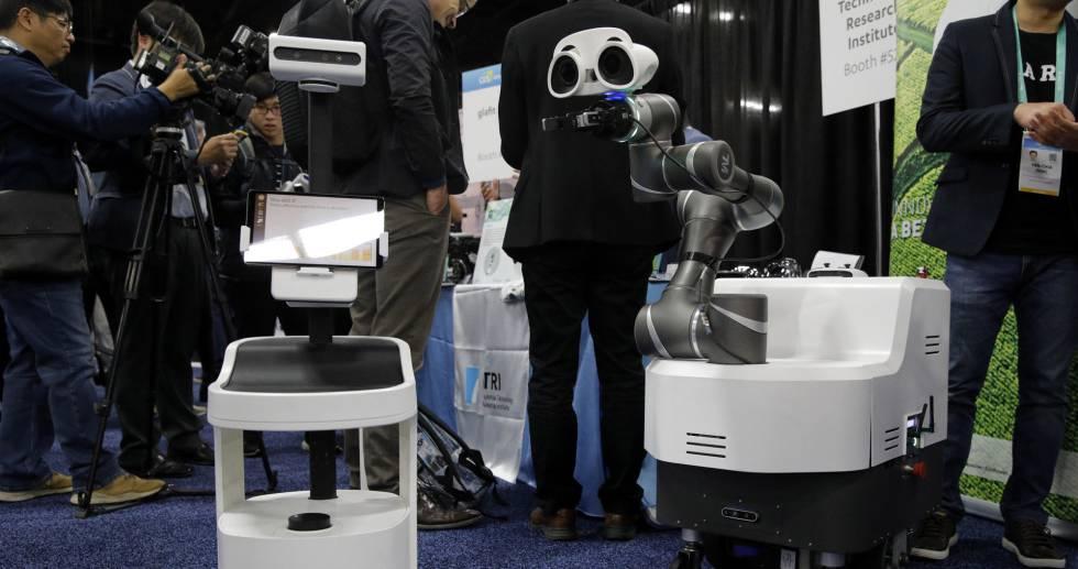 Asistentes al CES de Las Vegas, en un exhibidor donde se muestran dos dispositivos robóticos.