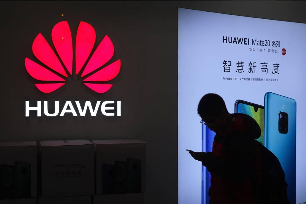 Un hombre pasa frente a una tienda de Huawei en Pekín.
