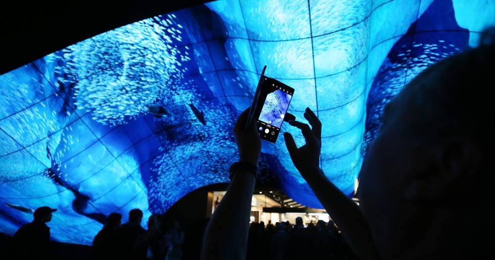 Un hombre saca una foto bajo una pantalla curva OLED de LG Electronics durante el CES 2020