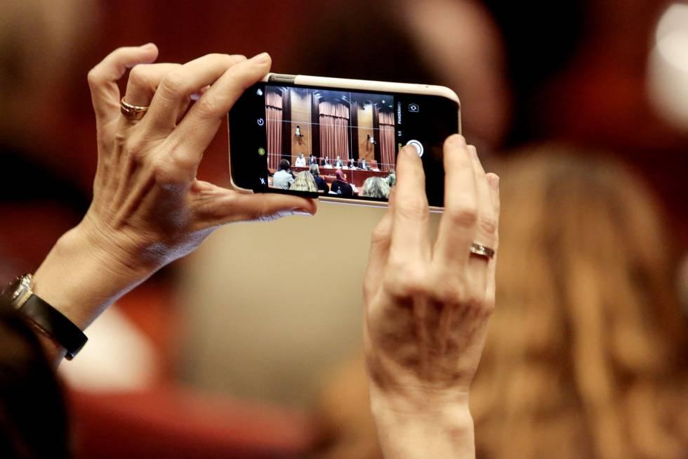 Una periodista toma una foto con su iPhone en una sesión del Parlamento de Cataluña el pasdo 28 de enero.