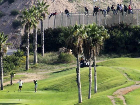Inmigrantes saltando la valla en Melilla: A un lado el lujo del golf y al otro la miseria más extrema.