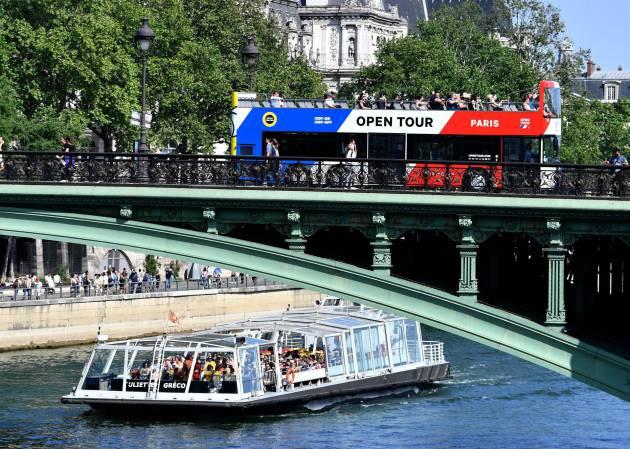 Turistas disfrutan de un viaje en bote en el Río Sena, en París. Foto