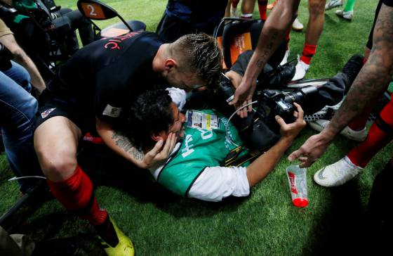 Ivan Rakitic sustenta a cabeça do fotógrafo Yuri Cortez depois do segundo gol marcado por Mario Mandzukic.