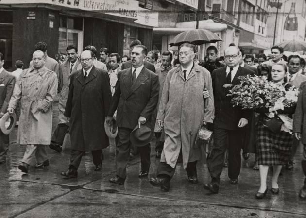 Diego Rivera camina junto a César Martino, Lázaro Cárdenas y Andrés Iduarte que lo sostiene del brazo detrás del coche fúnebre con los restos de Frida en 1954